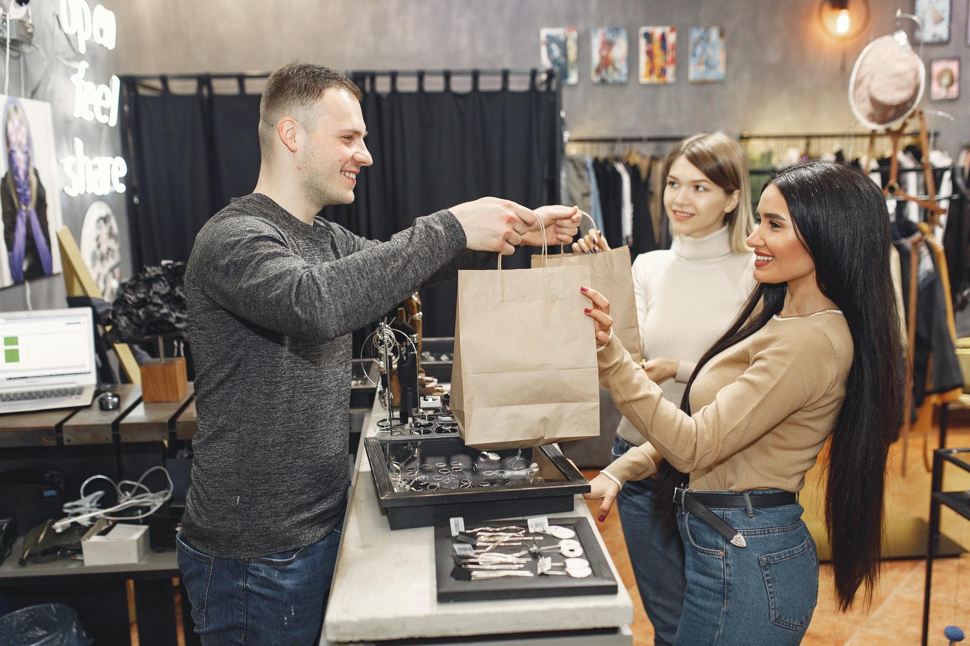 man handing shopping woman a bag at checkout