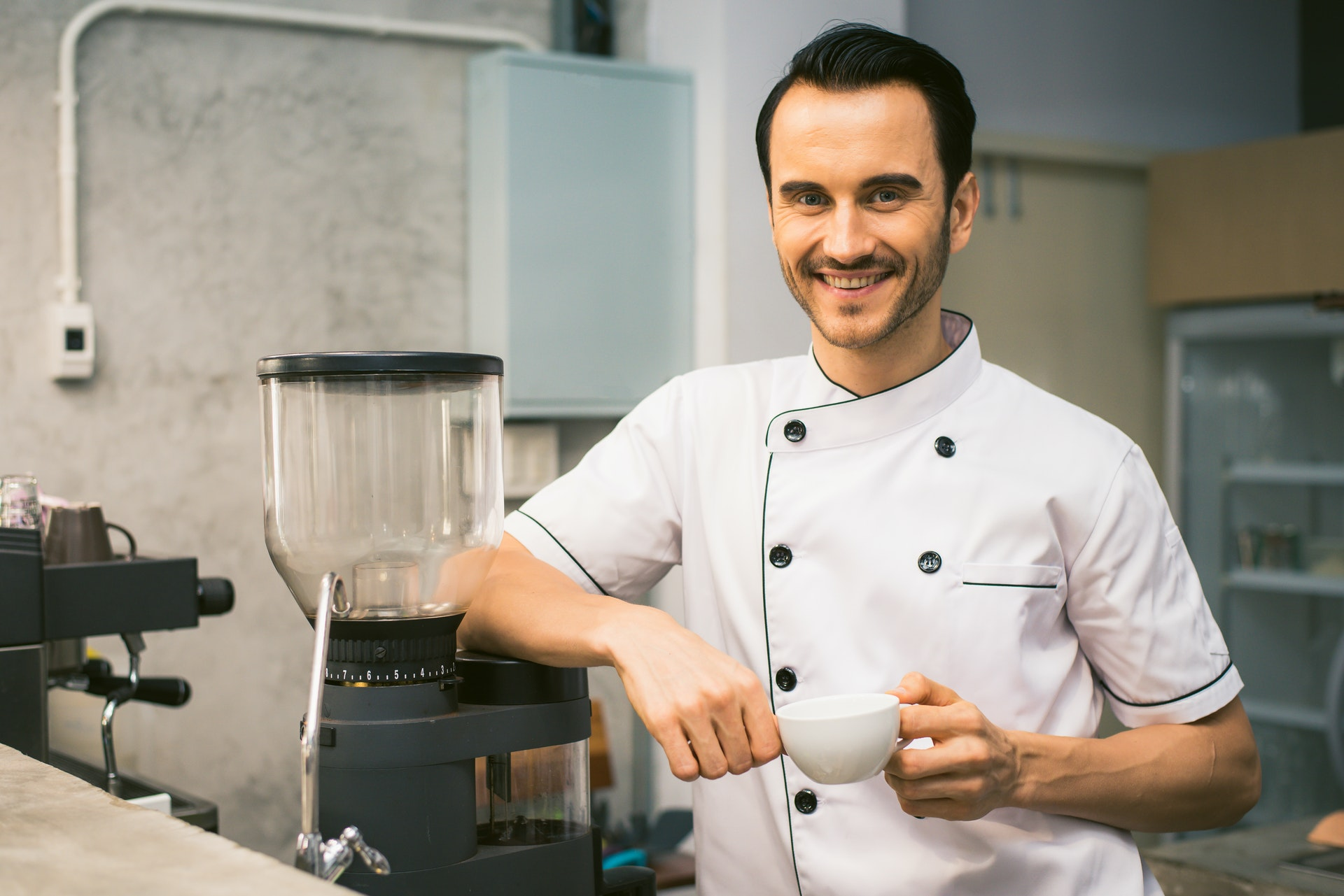 chef standing at coffee maker with cup in hand