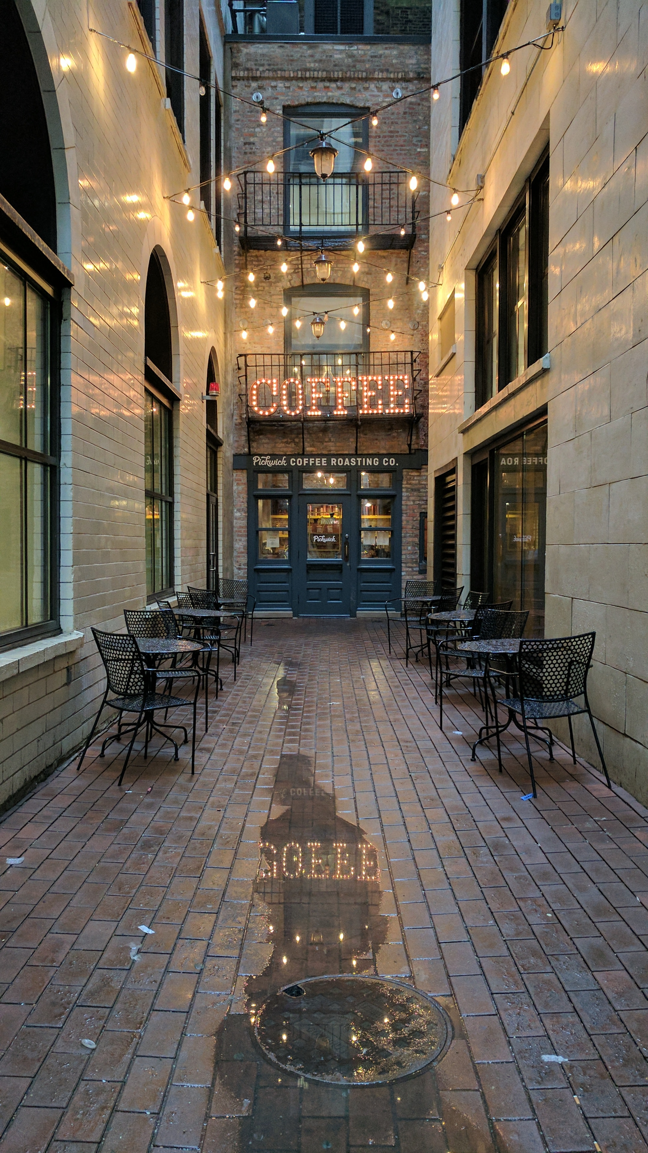 Exterior of blue cafe in alleyway with chairs