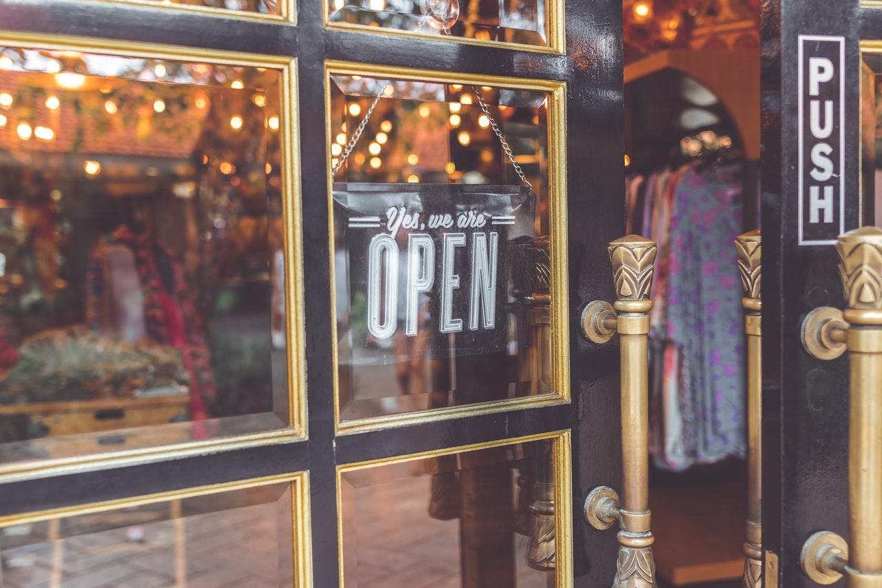 open sign handing in clothing shop door