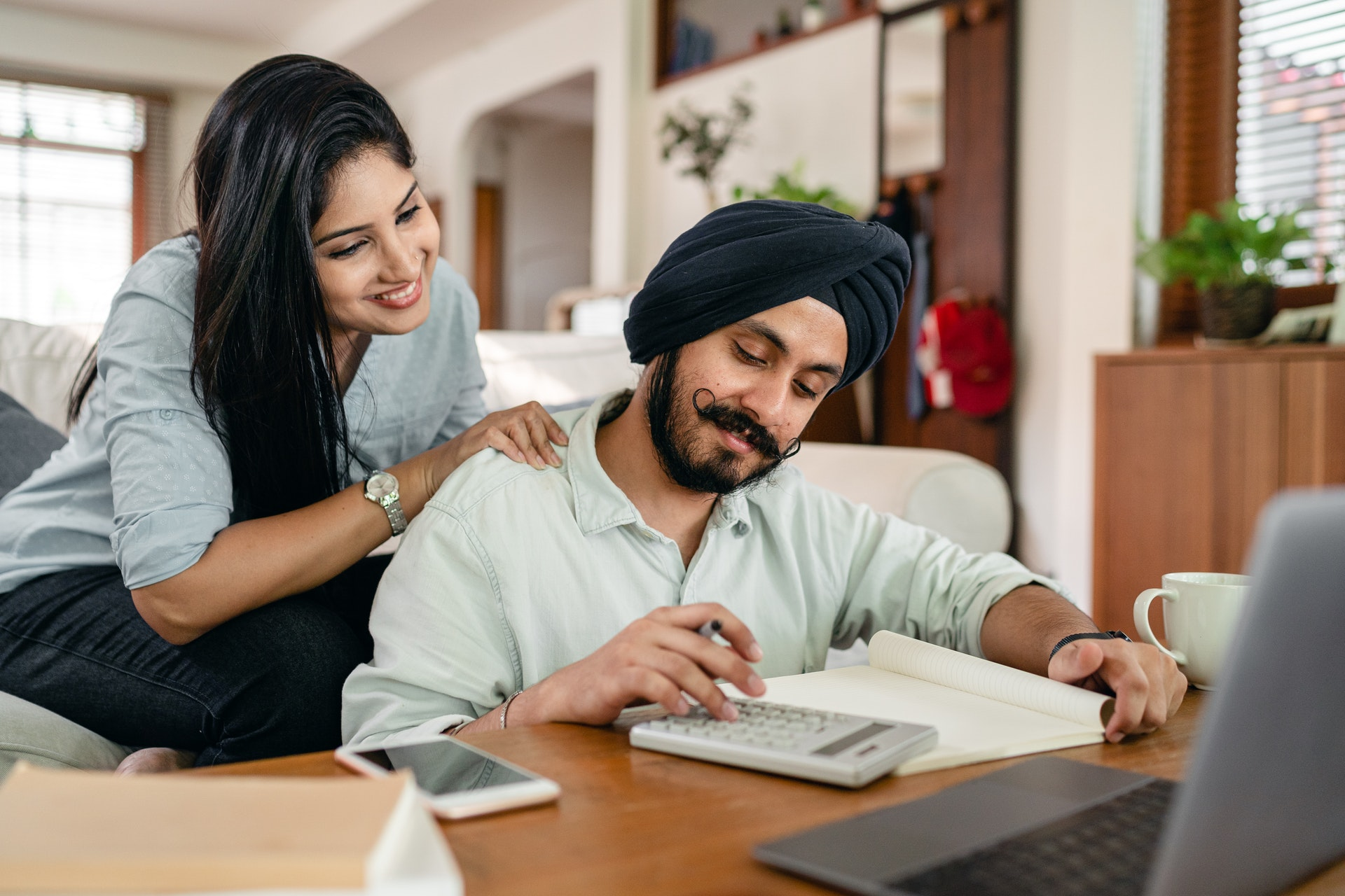 Man with turban and woman working with calculator and notebook