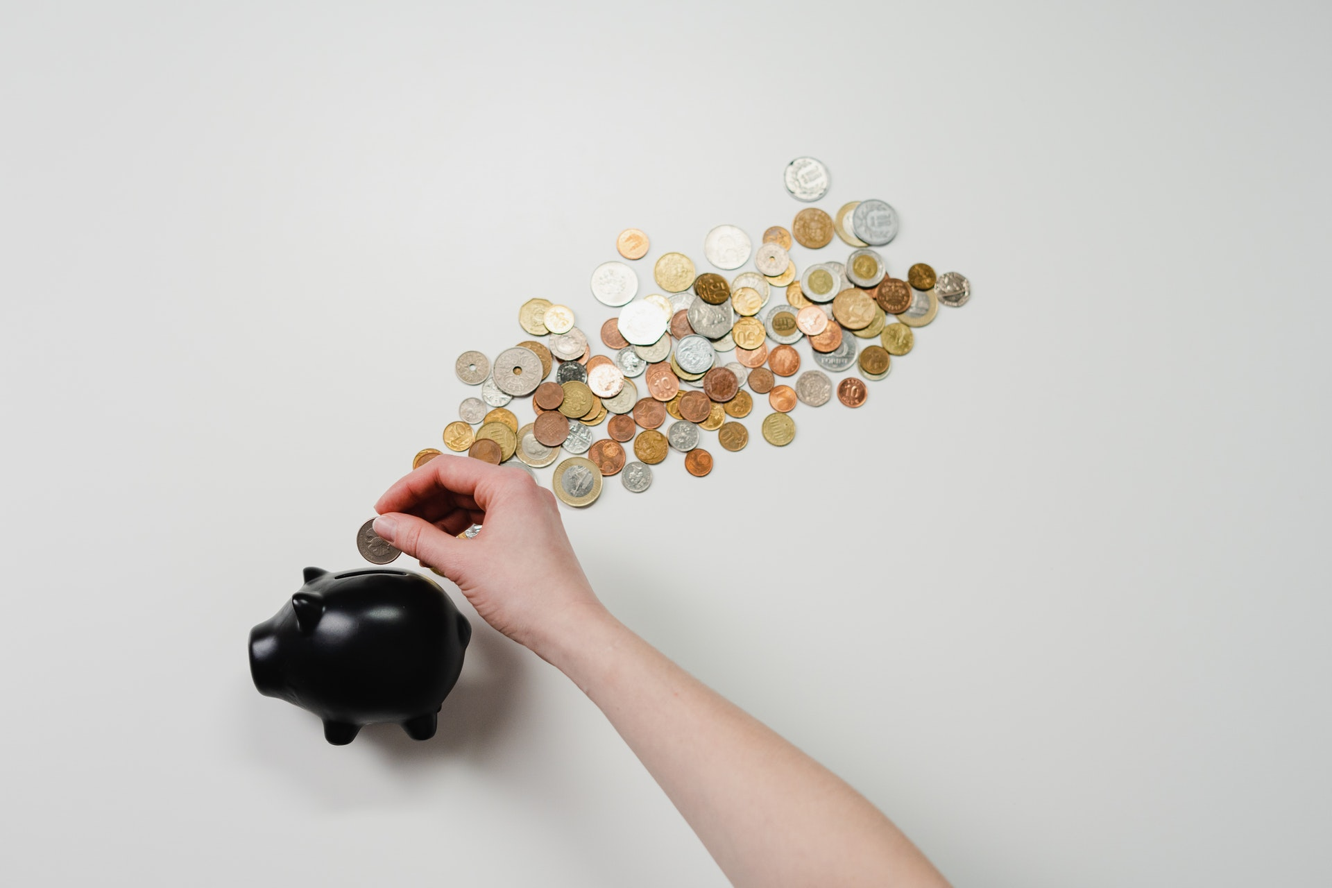 person inserting coin into black piggy bank with coins scattered around
