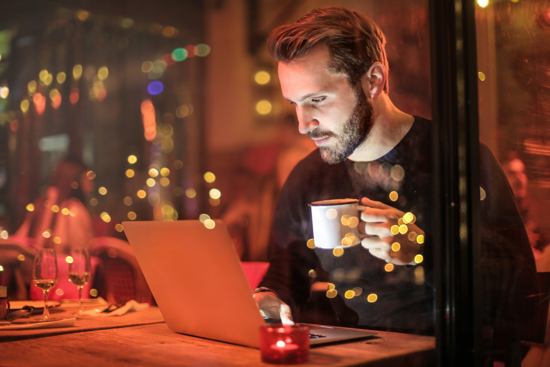 man working on laptop with coffee in hand at cafe