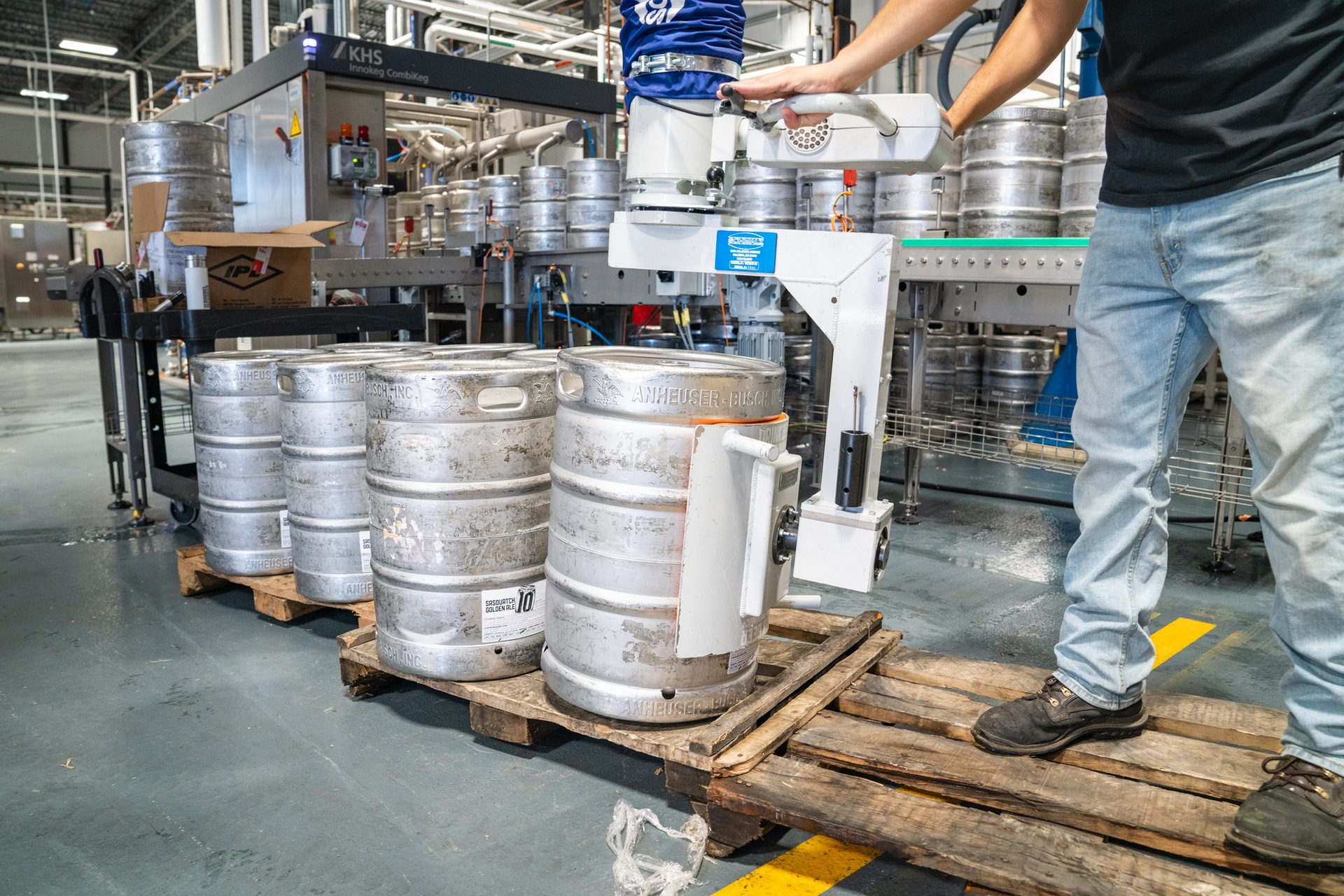 Man on palette with kegs in warehouse