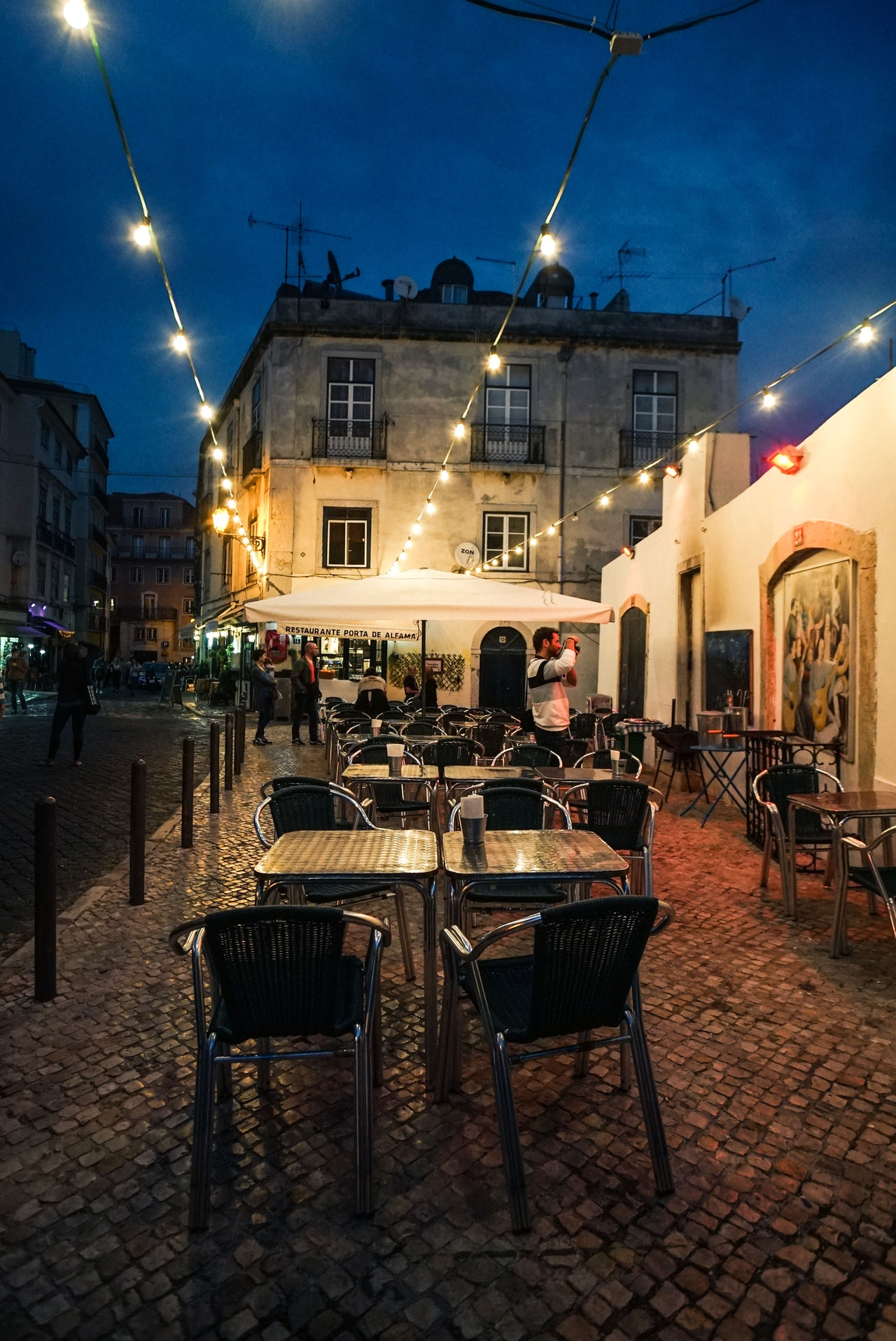 exterior of restaurant with chairs and people walking around