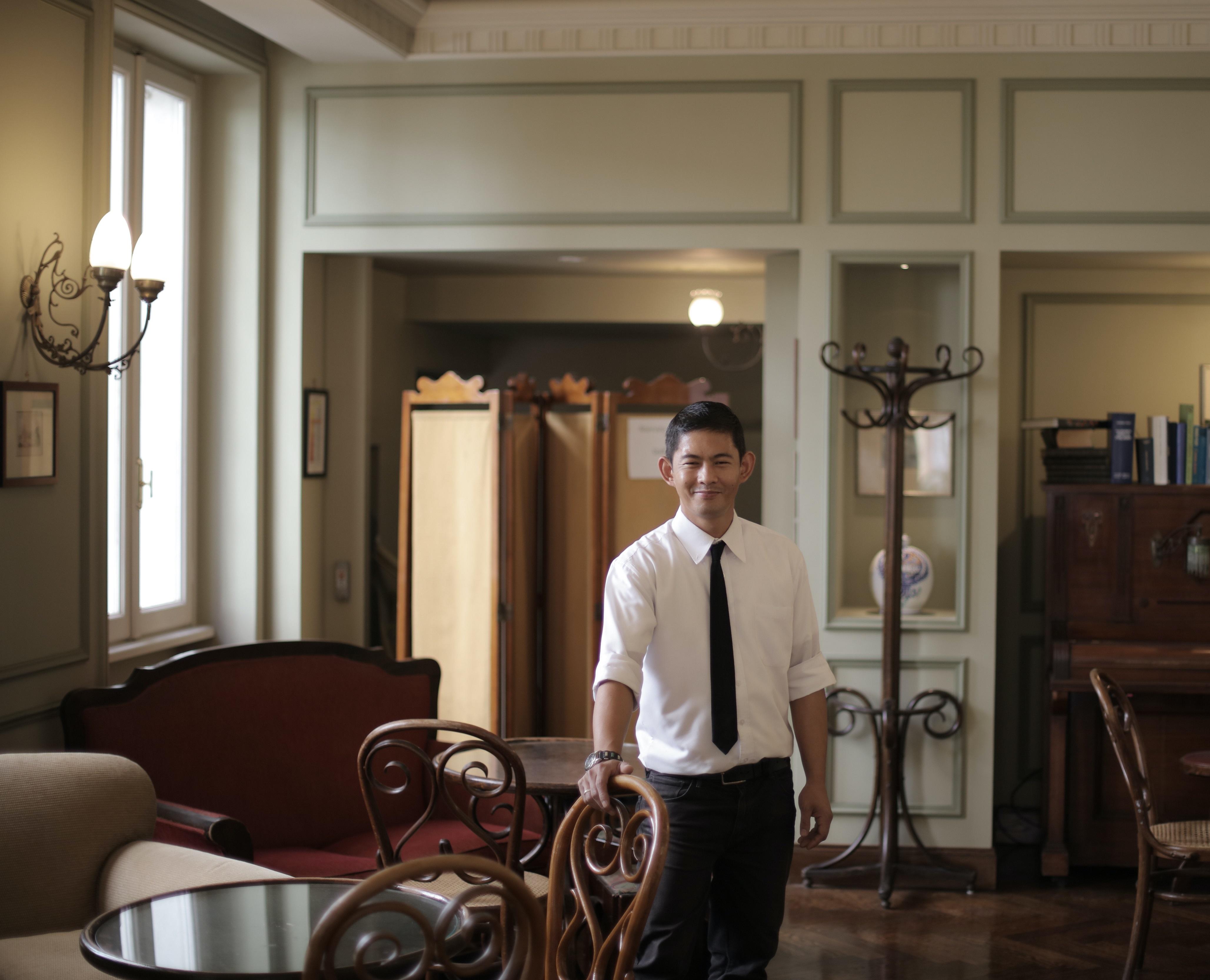 man in tie standing in antique looking room