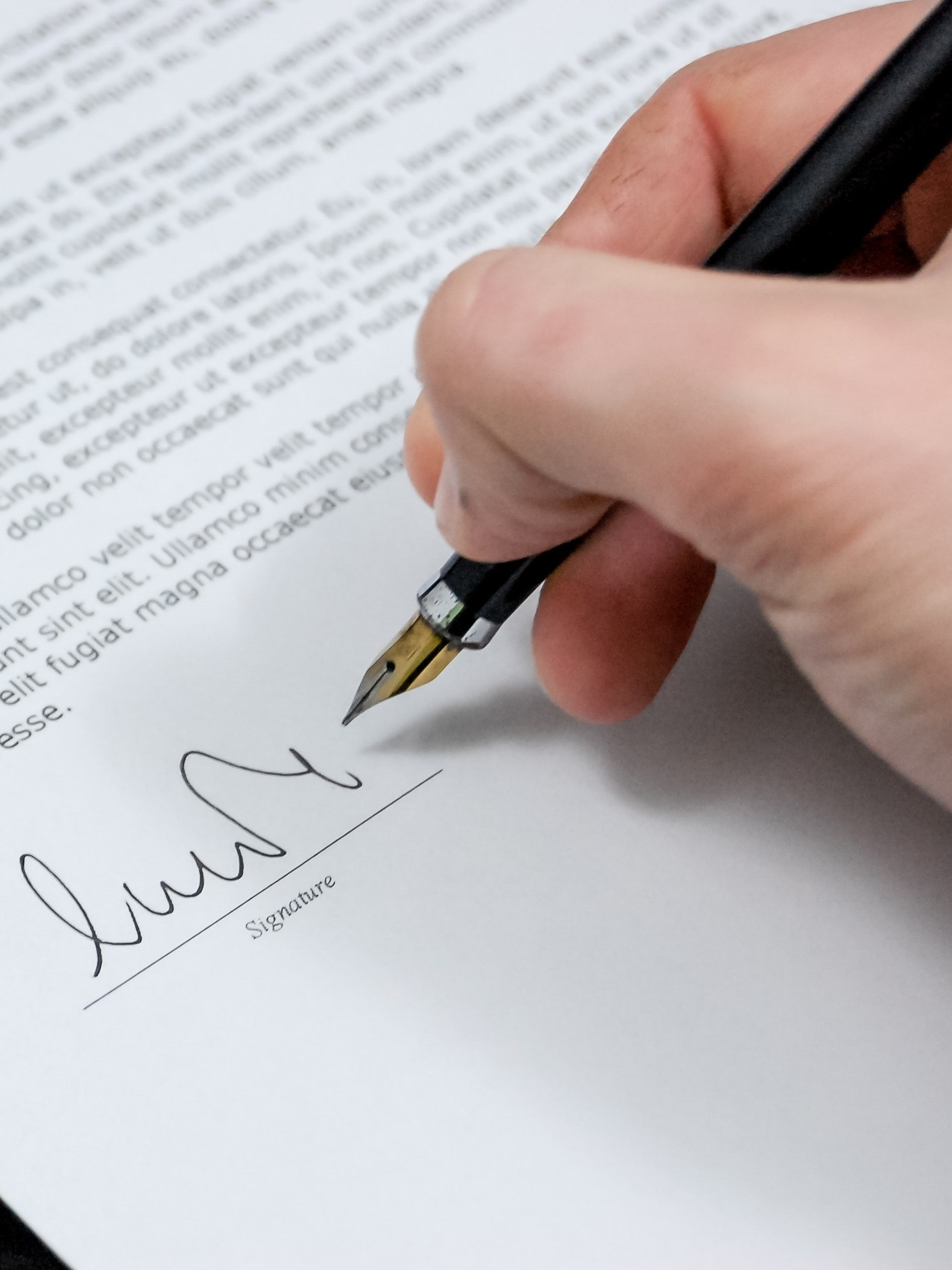 Hand putting down signature on white paper with pen