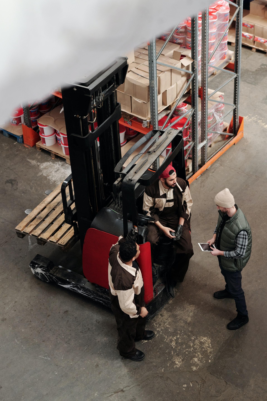 three men talking around forklift in warehouse