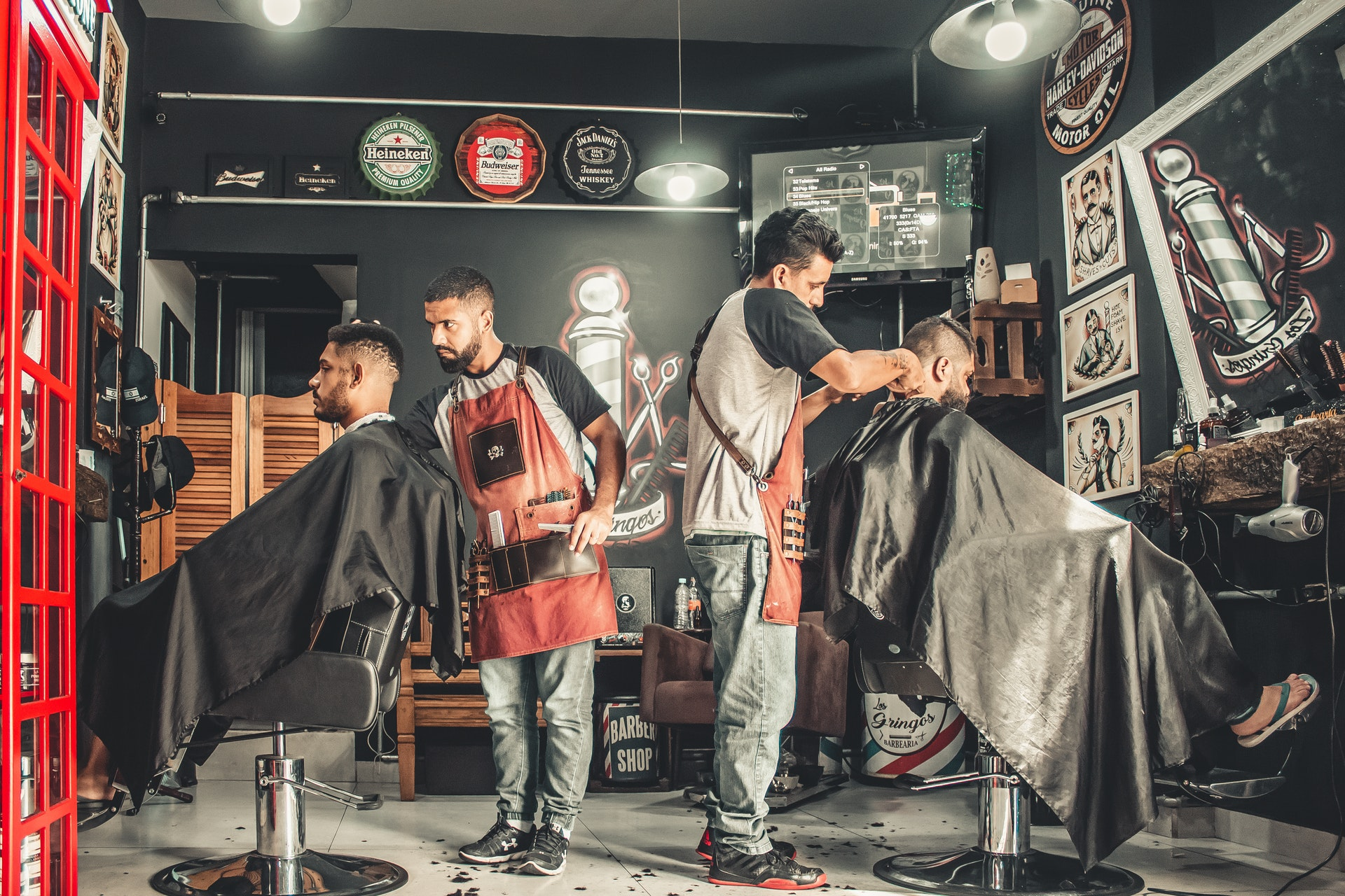 two men working in barber shop cutting hair