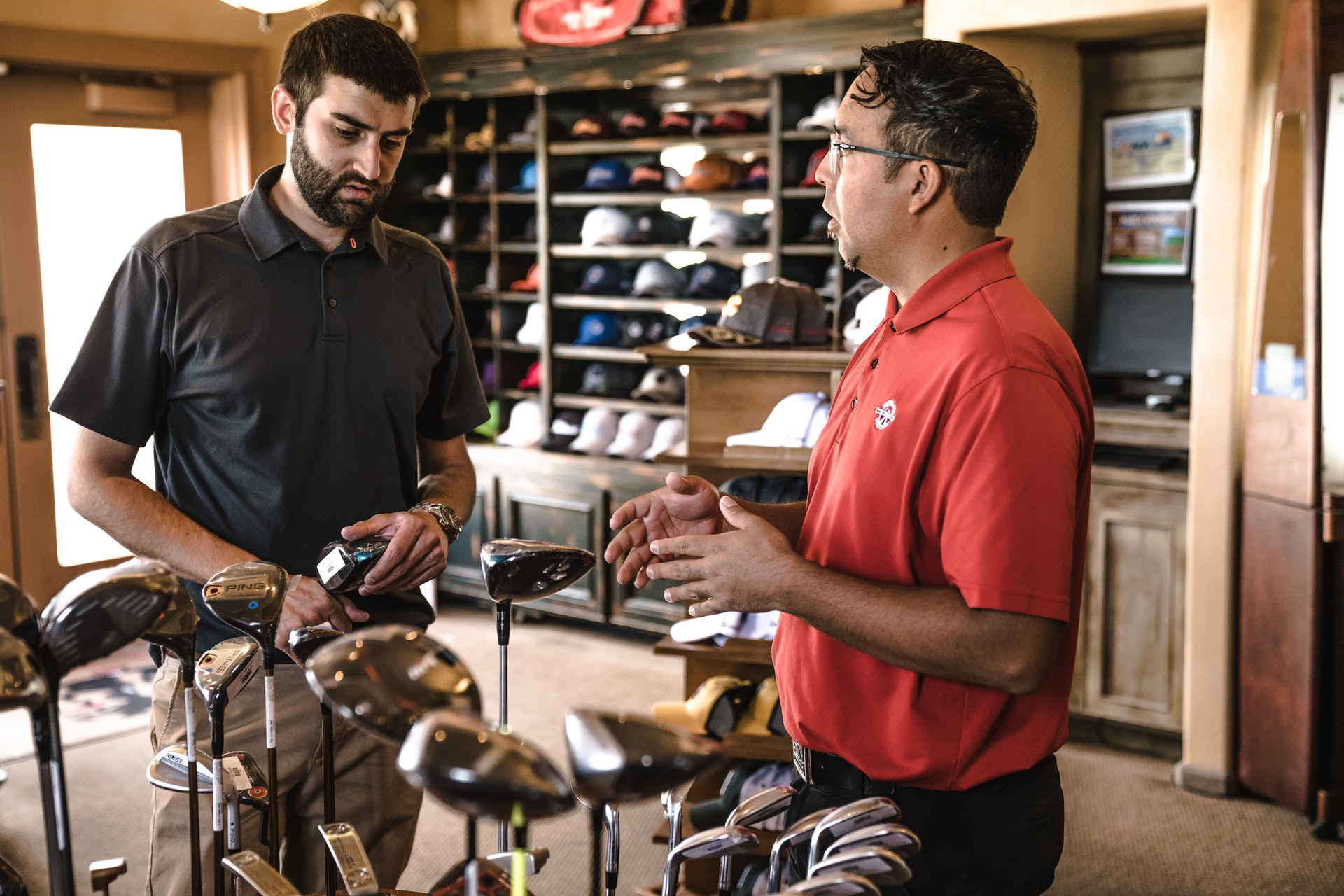 employer in golf shop talking to customer