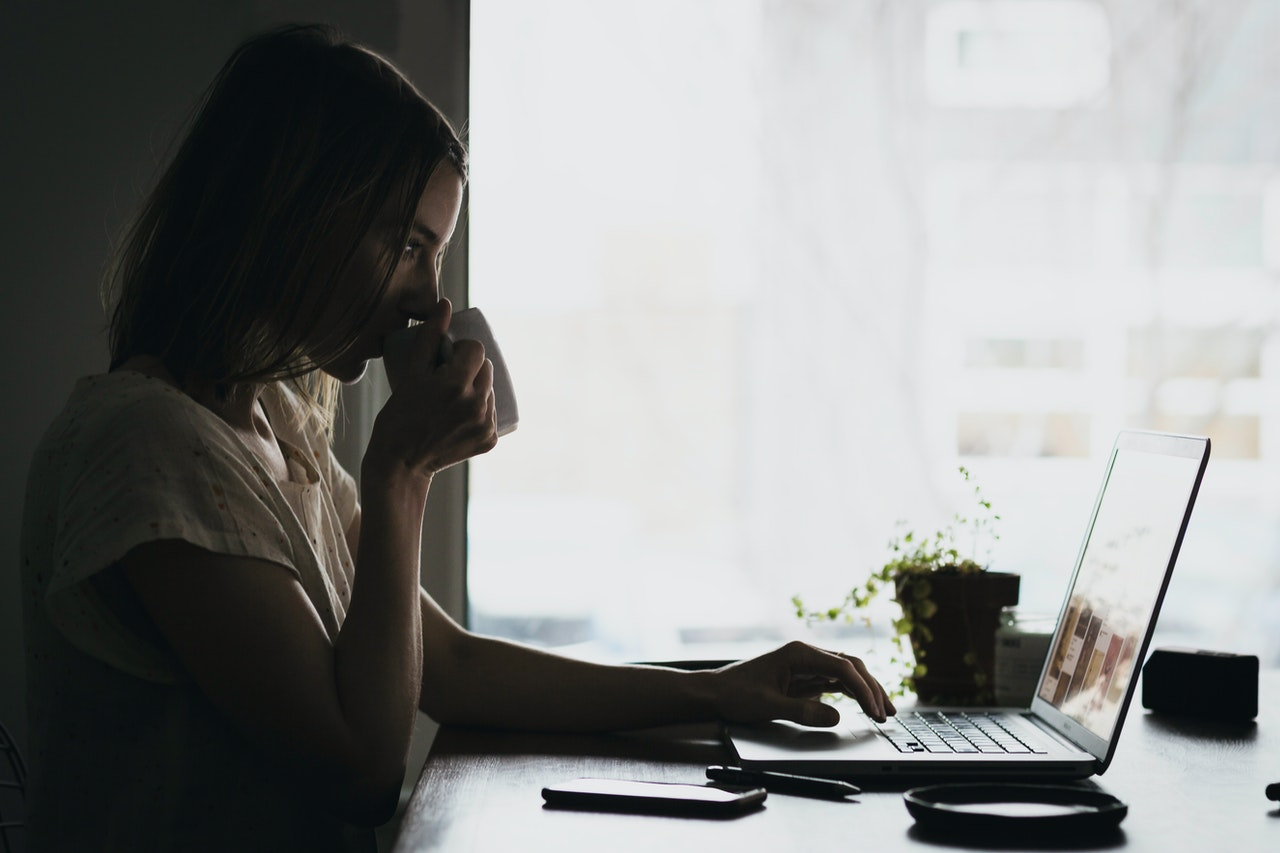 woman drinking cup of coffee while working on laptop