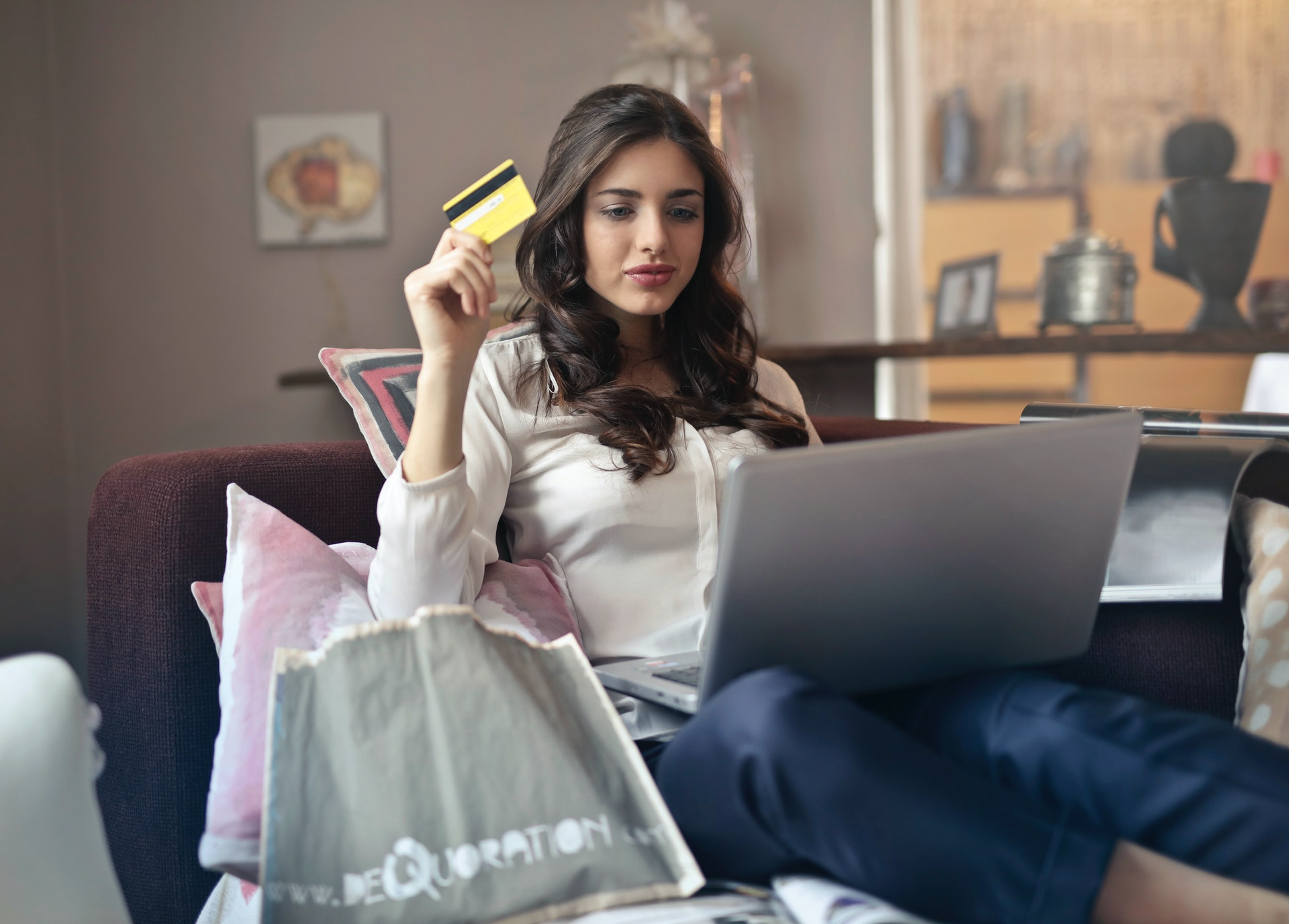 woman with laptop on sofa holding credit card